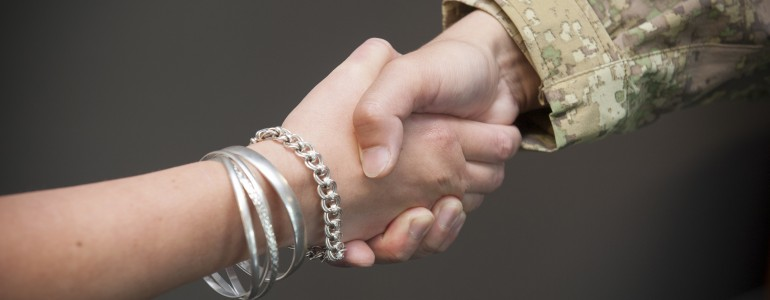 Two people shaking hands, one of them in uniform