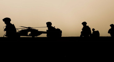 Silhouettes of soldiers patrolling with helicopter in background